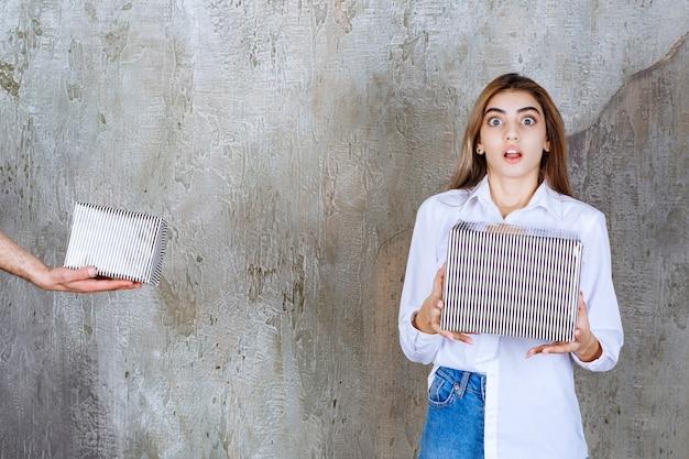 コンクリートの壁に立っている白いシャツを着た女の子は、銀のギフトボックスを提供されており、驚いておびえているように見えます。