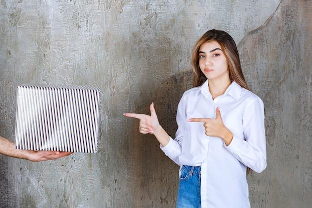 コンクリートの壁に立っている白いシャツの女の子は、銀のギフトボックスを提供されており、思慮深く見えます