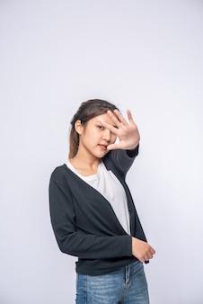 Девушка в белых джинсах стрейч и делает знак запрета руки на белой стене.