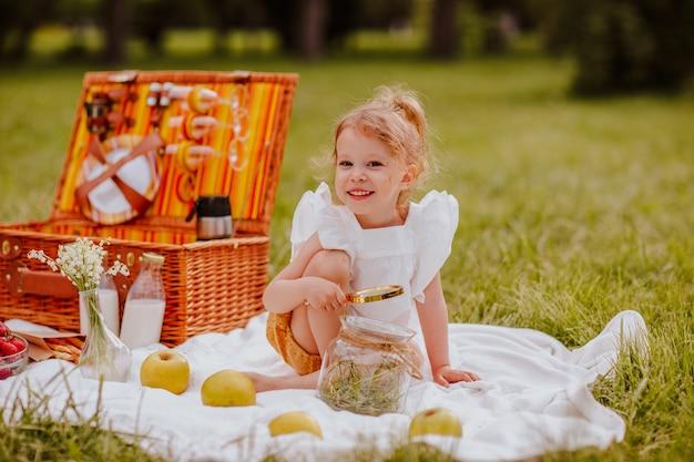 ピクニックに座ってビスケットでポーズをとる白い夏のブラウスの女の子。夏時間。