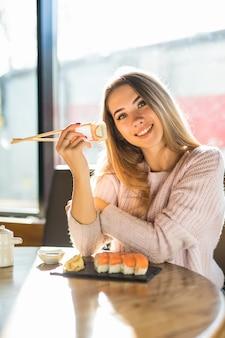 Девушка в белом свитере ест суши на обед в небольшом кафе