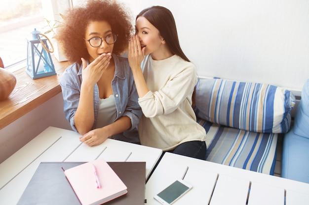 Девушка в белом свитере что-то шепчет на ухо подруге. афроамериканская девушка задается вопросом. она поражена и кладет руку на рот.