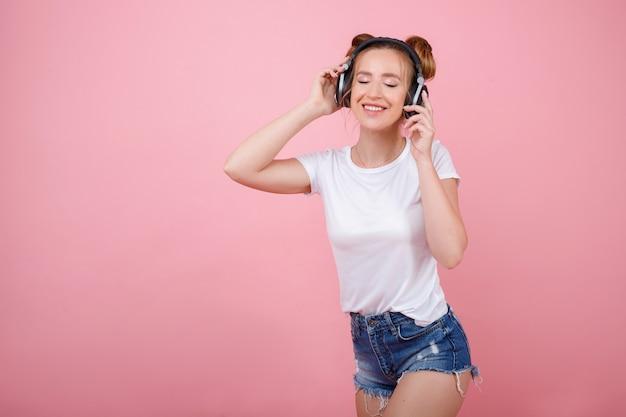 Девушка в белой футболке слушает музыку в наушниках на розовом пространстве