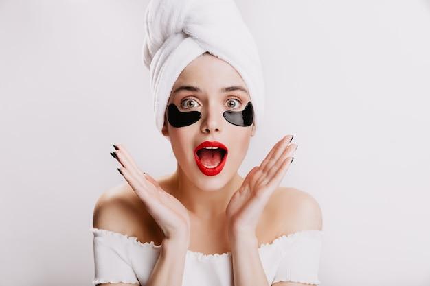하얀 수건을 입은 소녀가 놀람에 입을 열었습니다. 눈 아래 검은 패치 포즈 빨간 립스틱을 가진 여자.