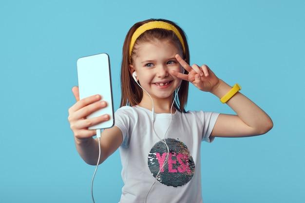 Девушка в белой футболке и наушниках делает селфи на мобильном телефоне и показывает мир