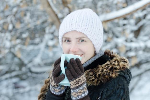 マグカップからお茶を飲む冬服の女の子。側面図。閉じる