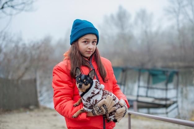 겨울 옷에 소녀입니다. 오렌지 재킷, 모자와 스카프에 십 대 소녀. 소녀와 치와와.