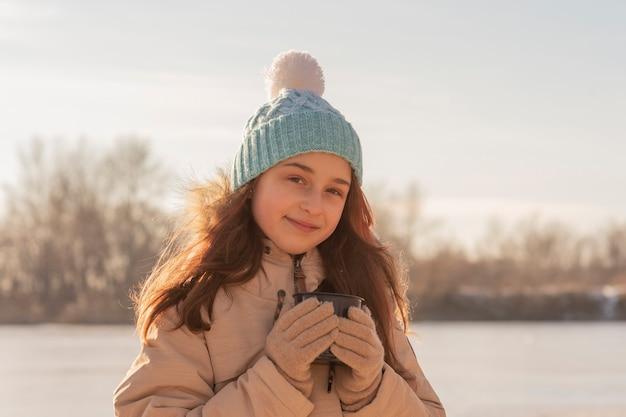Девушка зимой в бежевой куртке. девушка пьет чай на улице. подросток пьет из чашки чая
