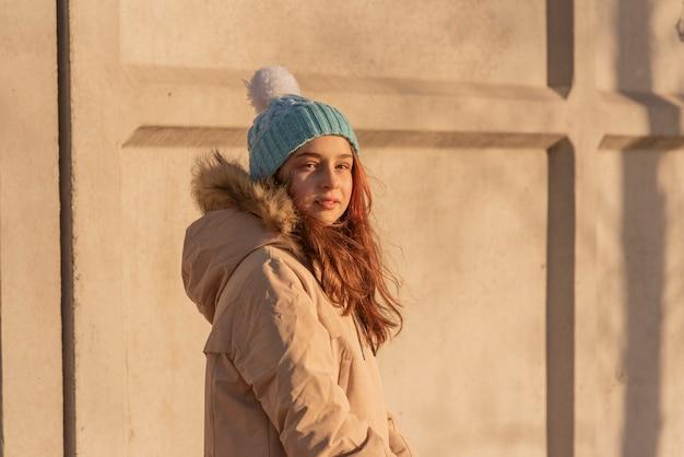 Девушка зимой в бежевой куртке. девушка позирует в синем с белой шляпе и зимней теплой одежде.