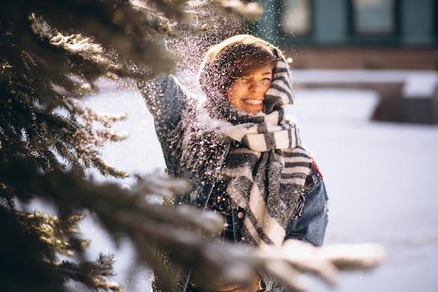 Девушка зимой в джинсовой куртке на открытом воздухе у ели