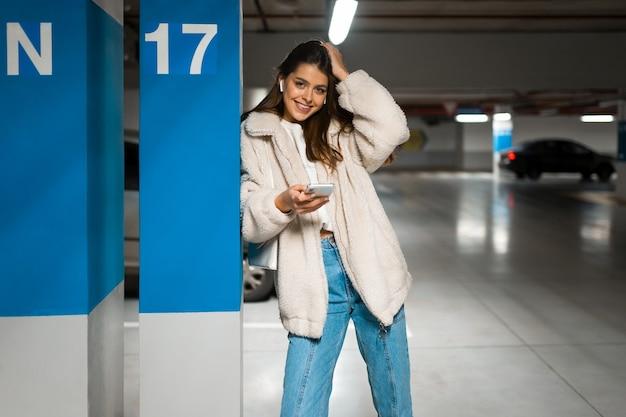 무선 이어폰과 손에 휴대 전화 소녀