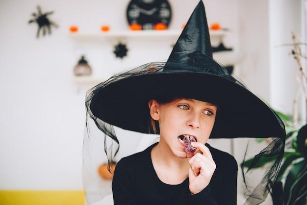 Девушка в костюме ведьмы ест мягкую желейную конфету