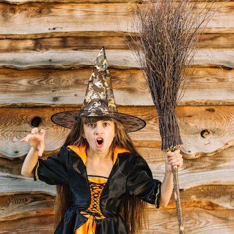 Girl in witch costume showing horror with broomstick