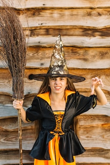 Girl in witch costume showing reach out hand with broomstick