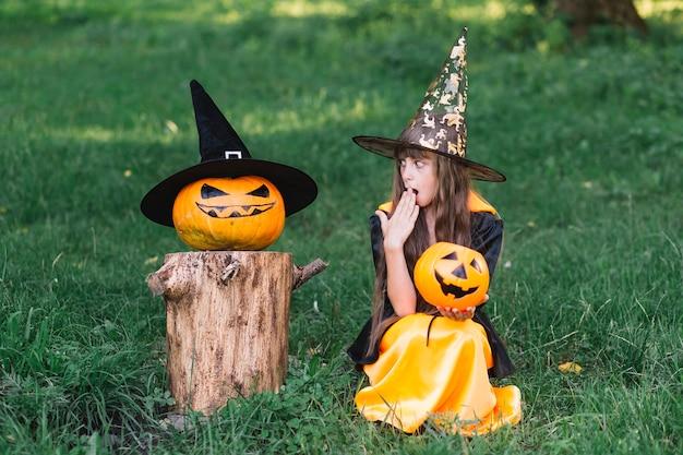 Девушка в костюме ведьмы, показывающая удивление возле тыквы