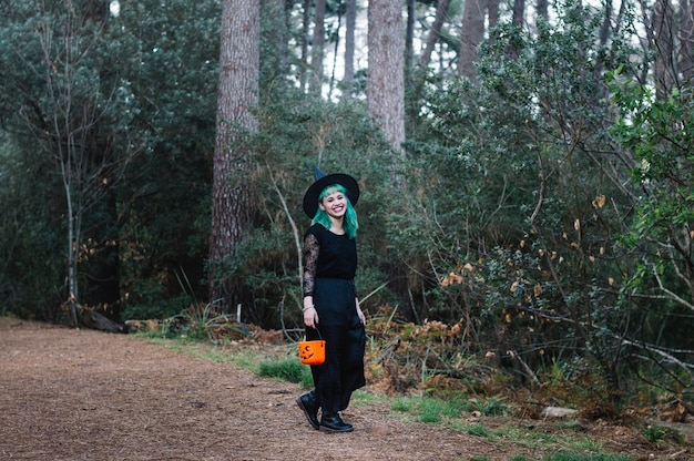 Девушка в шляпе ведьмы смеется в лесу