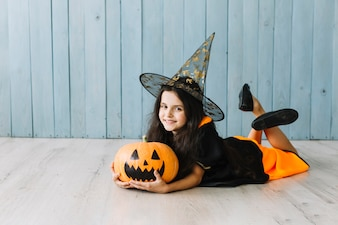 Girl in witch suit lying on floor with pumpkin