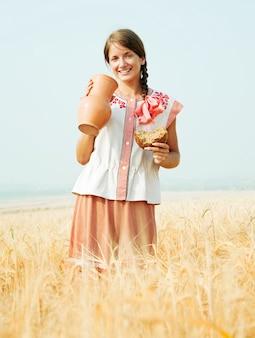 Девушка с хлебом и кувшином в поле