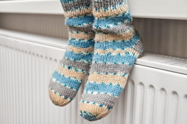모직 양말을 입은 소녀가 라디에이터에 발을 따뜻하게합니다.