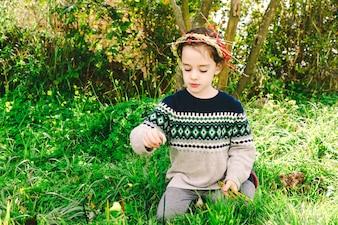 Girl in wreath sticking sticks in ground
