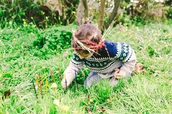 Girl in wreath sticking sticks in nature