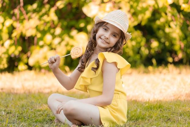 夏に公園の芝生の上に黄色い服と帽子をかぶった女の子が座っています。高品質の写真