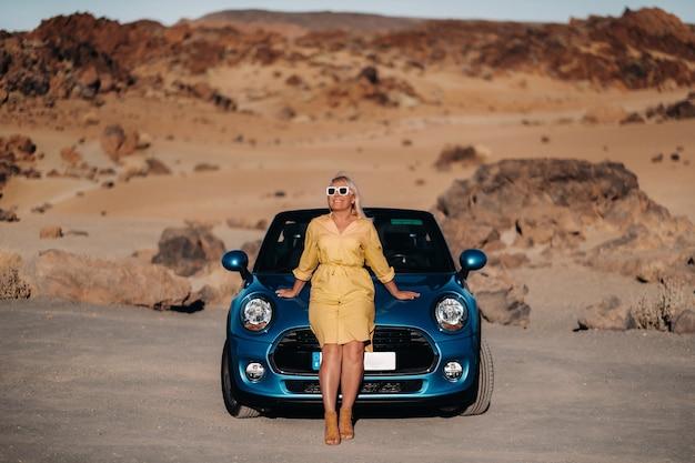 テネリフェ島、カナリア諸島、山々のある人けのない谷をコンバーチブルでロードトリップを楽しんでいる黄色いドレスの女の子。