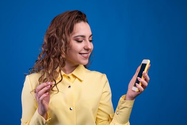 Девушка в желтом платье текстовые сообщения на своем смартфоне концепция небольших текстовых сообщений