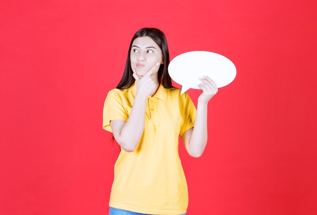 卵形の情報ボードを保持し、思慮深く、ためらうように見える黄色のドレスコードの女の子