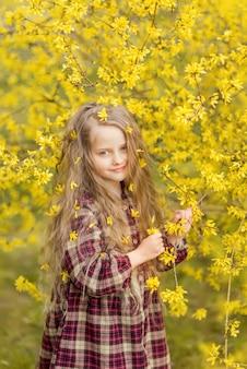 黄色い花の少女。レンギョウを背景にした子供。彼女の髪に花を持つ子供の春の肖像画