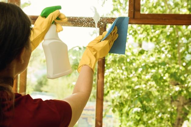 洗剤で黄色の手袋の少女は、プラスチックの窓を洗います。家庭用および窓拭き用の清掃会社