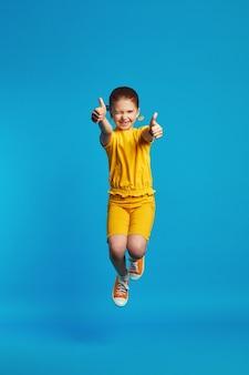 Девушка в желтом костюме прыгает, показывая палец вверх против синего