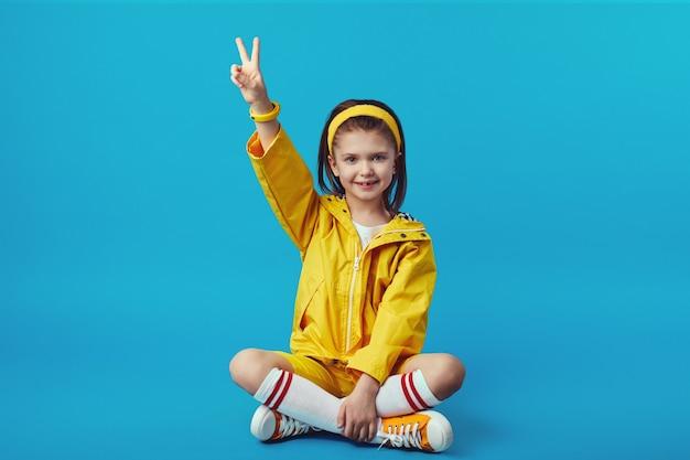 Девушка в желтом наряде показывает жест мира, сидя со скрещенными ногами