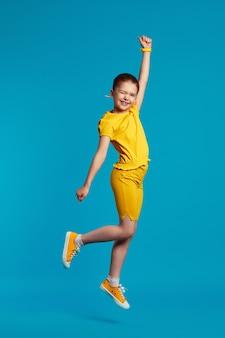 Девушка в желтом наряде улыбается и поднимает руку, подпрыгивая на синем