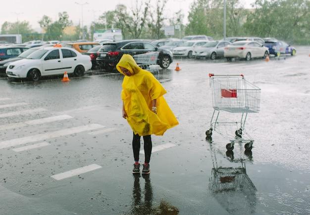 노란 우비를 입은 소녀는 주차장에서 비가 내리고 혼자 서 있습니다.