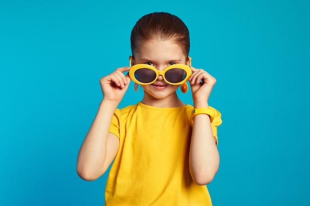 Девушка в желтой рубашке поправляет солнцезащитные очки и смотрит в камеру через Premium Фотографии
