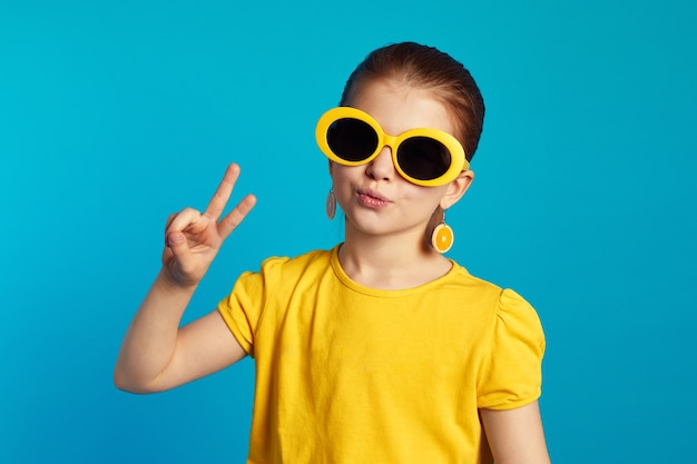 Девушка в желтой рубашке и солнечных очках держит губы округлыми и делает жест мира
