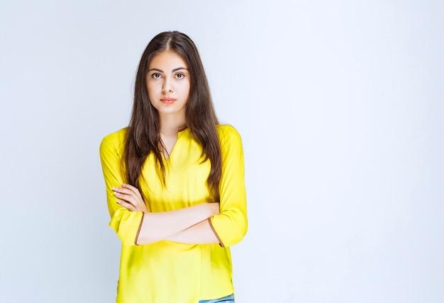 Девушка в желтой рубашке скрещивает руки и дает профессиональные позы.