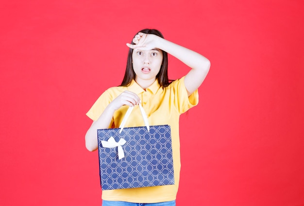 青い買い物袋を持っている黄色いシャツを着た女の子は、恐怖を恐れているように見えます。