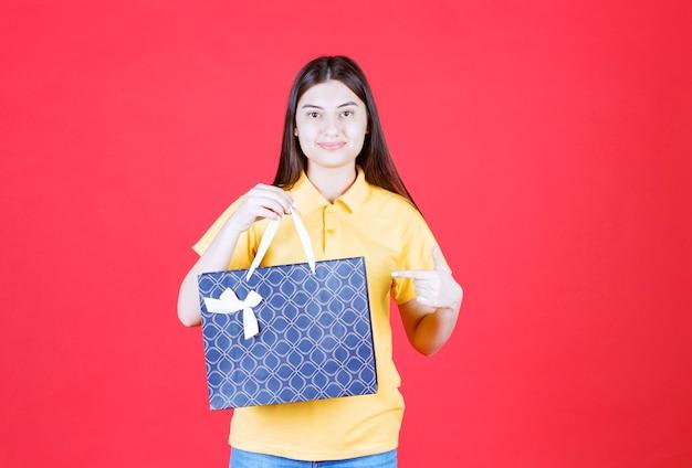 Девушка в желтой рубашке держит синюю сумку для покупок