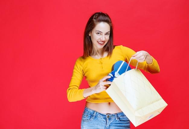 Девушка в желтой рубашке держит картонную сумку для покупок, берет синюю подарочную коробку и чувствует себя удивленной