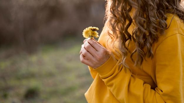 꽃 중간보기를 들고 노란색 셔츠에 여자