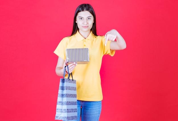 Девушка в желтой рубашке держит сумку для покупок и серебряную подарочную коробку и зовет человека рядом с собой