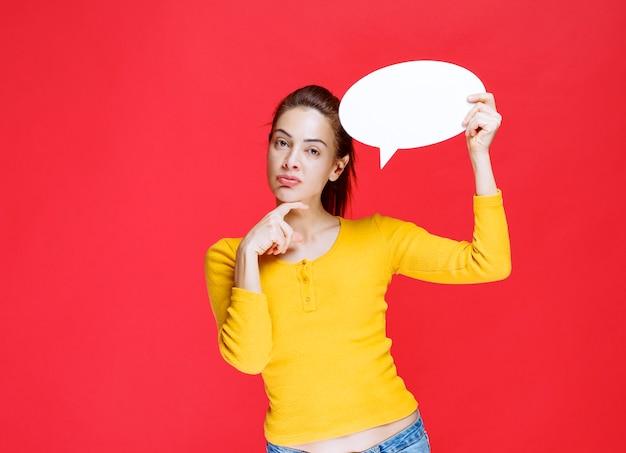 卵形の情報ボードを保持し、混乱して思慮深く見える黄色いシャツの女の子