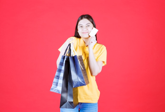 Девушка в желтой рубашке держит несколько синих сумок и кредитной карты.