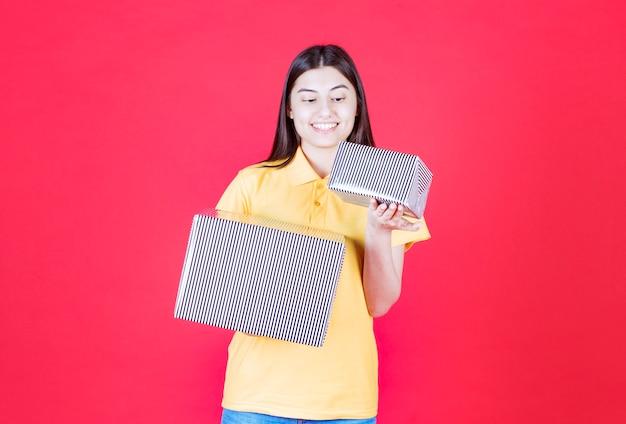 銀のギフトボックスを保持している黄色いシャツの女の子。