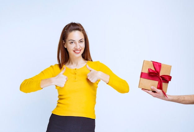 노란색 셔츠를 입은 소녀는 빨간 리본이 달린 골판지 선물 상자를 제공하고 긍정적 인 손 기호를 표시합니다.