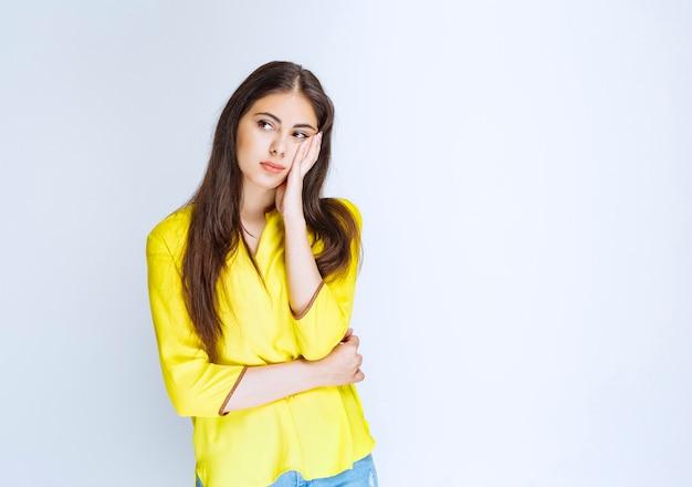 黄色いシャツを着た女の子は混乱して疑わしいように見えます。