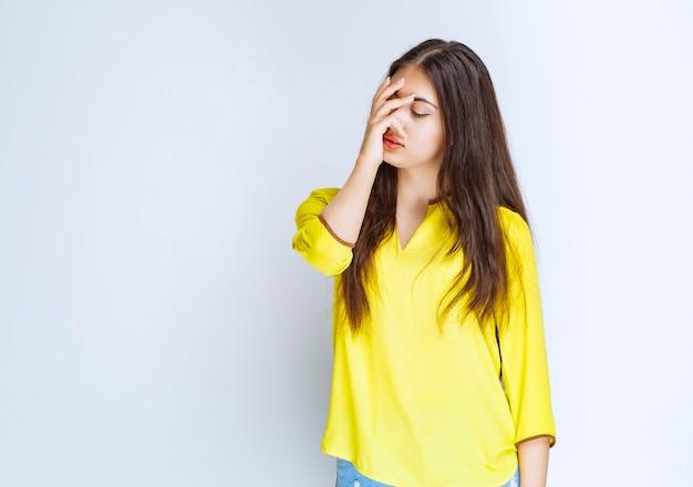 黄色いシャツを着た女の子は、疲れているように見えるか、頭痛がします。