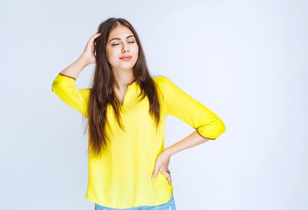노란 셔츠를 입은 소녀는 피곤해 보이거나 두통이 있습니다.